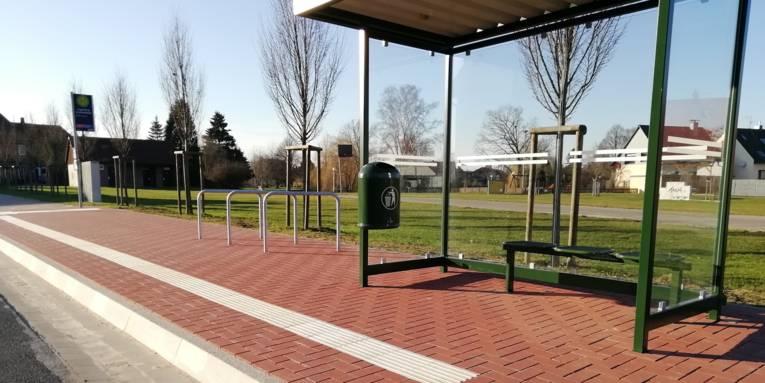 Bushaltestelle mit Überdachung, Sitzgelegenheit, hohem Bürgersteig, Fahrradbügeln und taktilem Bodenleitsystem