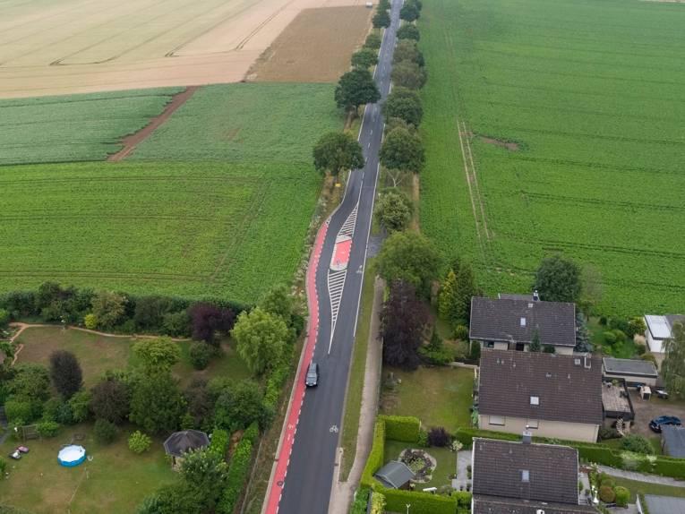 Luftbild einer Straße mit einem roten Streifen an der Seite