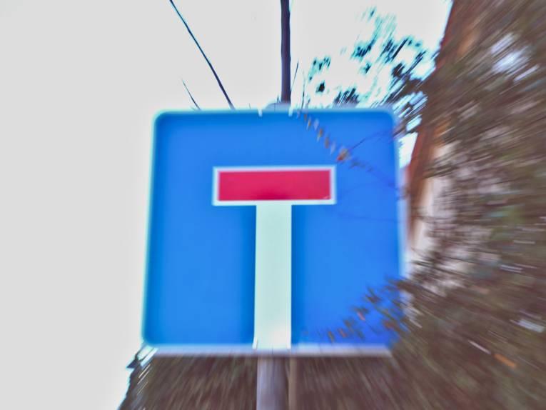 Reisszoom auf ein Schild, das auf eine Sackgasse hinweist.