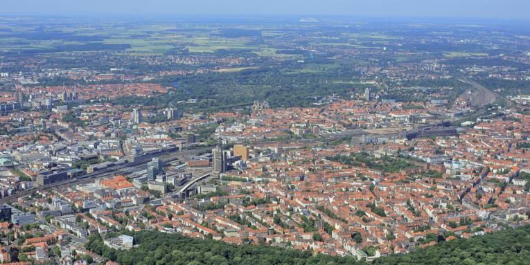 Innenstadt und Stadtwald Eilenriede liegen beieinander, Wohnhäuser, Geschäftsgebäude, Bahngleise und der Hauptbahnhof Hannover sind zu erkennen.