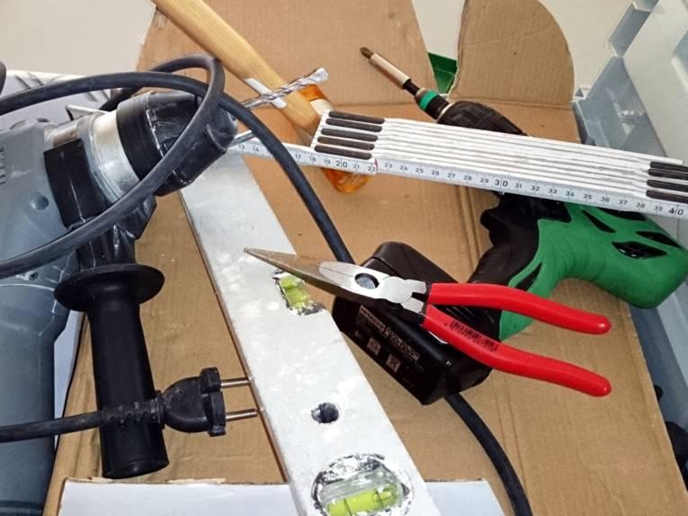 In einem Karton liegen verschiedene Werkzeuge, darunter Bohrmaschine, Zange, Wasserwaage, Akkuschrauber.