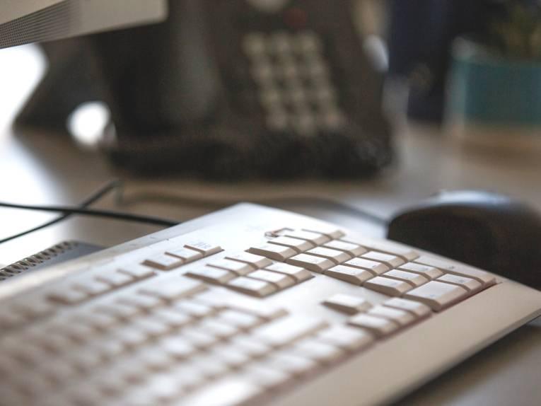 Blick auf ein Telefon, vorbei an einer Computertastatur und Computermaus.