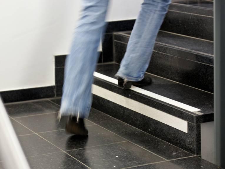 Blick auf die Füße einer Person, die eine Treppe hinauf steigt.