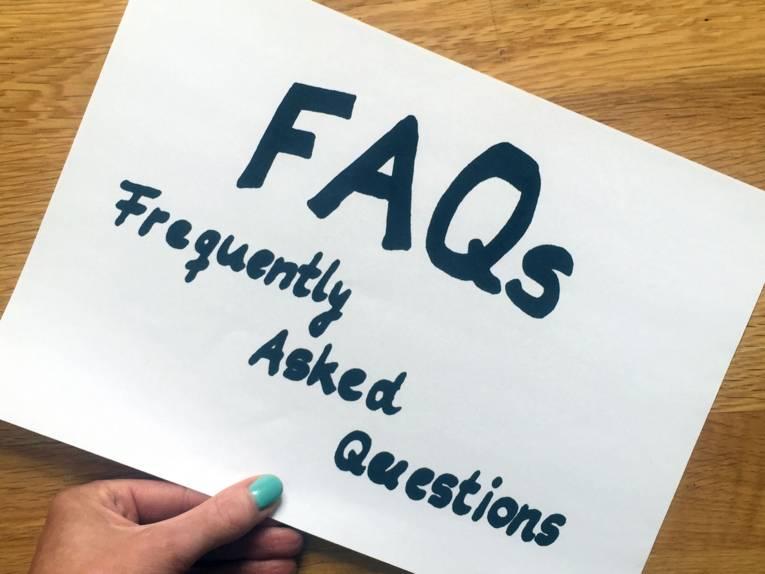 """Eine Hand und ein Zettel, auf dem """"FAQa - Frequently Asked Questions"""" steht."""