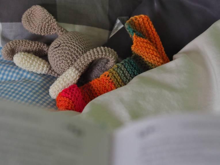 Blick über ein Buch auf ein Bett mit Kuscheltier.