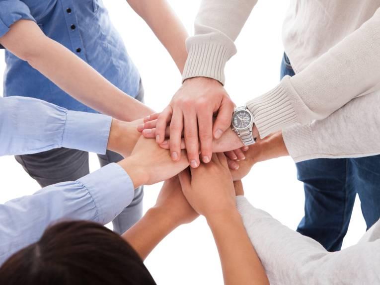 Fünf Personen stehen im Kreis und haben ihre Arme nach vorne ausgestreckt, um so ihre Hände übereinander zu legen.