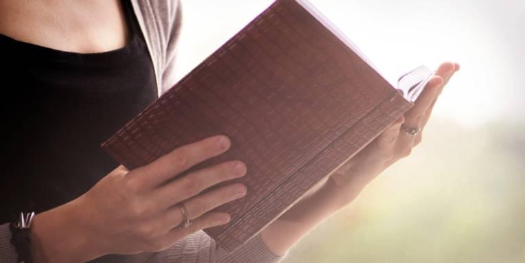 Eine Frau hält ein aufgeschlagenes Notizbuch in den Händen und blickt hinein.