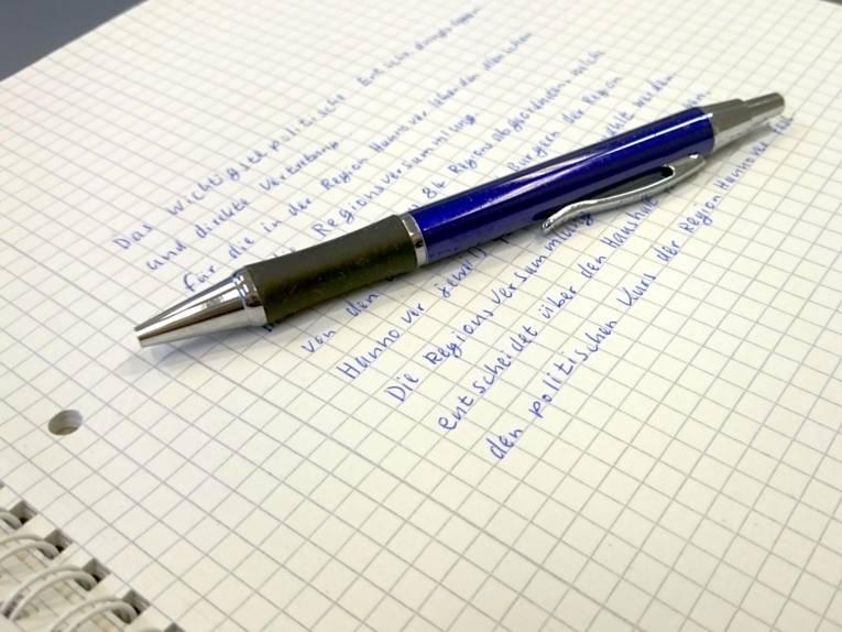 Das oberste Blatt eines Schreibblocks ist beschrieben. Obenauf liegt ein blauer Kugelschreiber.