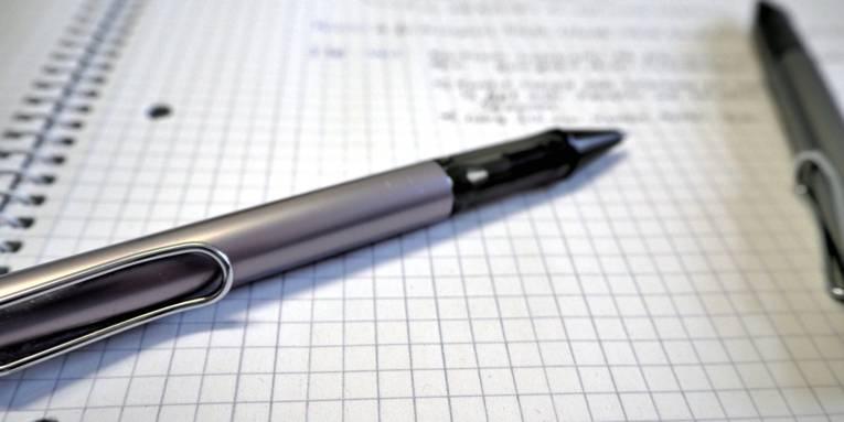 Ein Kugelschreiber liegt auf einem Schreibblock mit kariertem Papier. Handschriftliche Notizen stehen auf dem Papier.