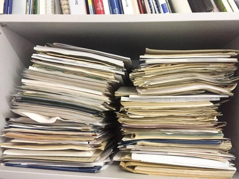 Ein Regal, in dem zwei Stapel Unterlagen, Akten, Hefter liegen und in dem Fach darüber befinden sich Bücher.