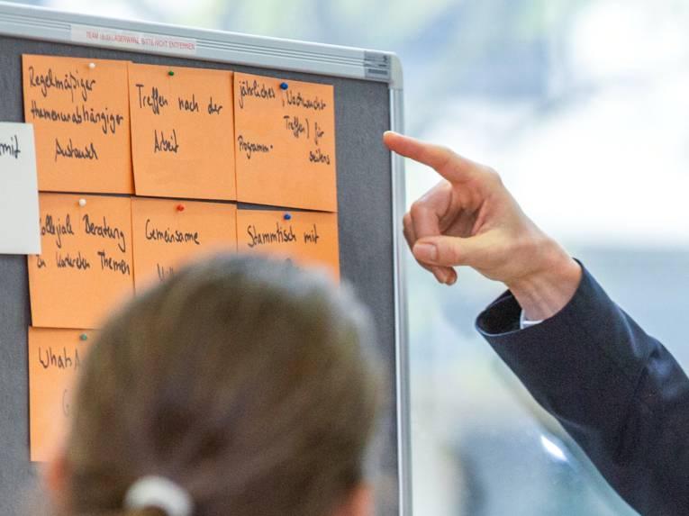 Eine Person schaut auf eine Metaplanwand. Dorthin zeigt eine andere Person mit dem Zeigefinger.