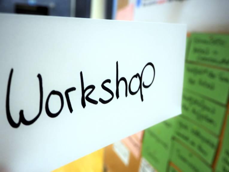 """Auf einem weißen Kärtchen steht mit der Hand geschrieben """"Workshop"""", dahinter ist eine Metaplanwand, an die weitere Kärtchen in anderen Farben geheftet sind."""