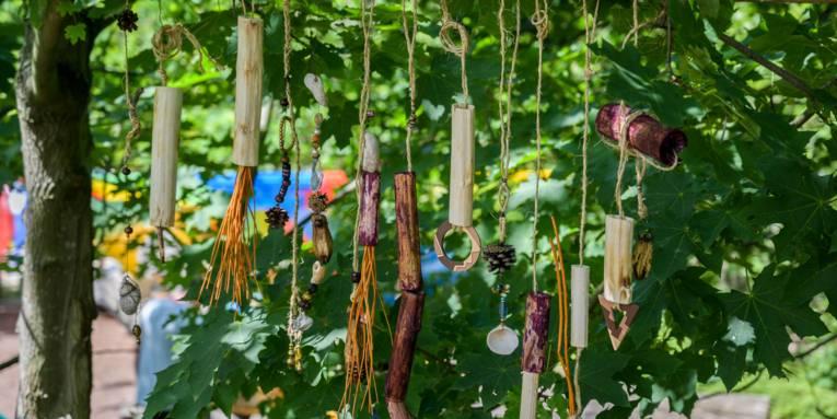 In einem Baum hängende Materialen, die eine Art Mobile ergeben und Töne erzeugen