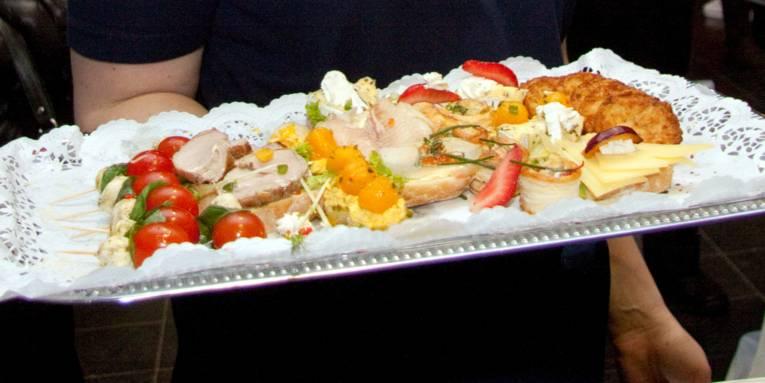 Tomaten und Mozzarella, Braten, Erdbeeren und andere Leckereien liegen auf einem Tablett, das eine Person mit einer Hand trägt.