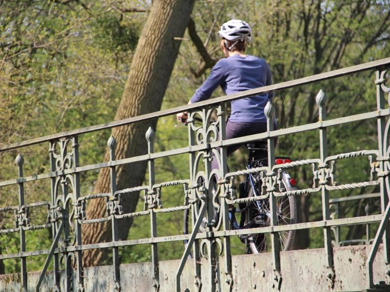 Eine Fahrradfahrerin, die einen Helm trägt, überquert eine Brücke.