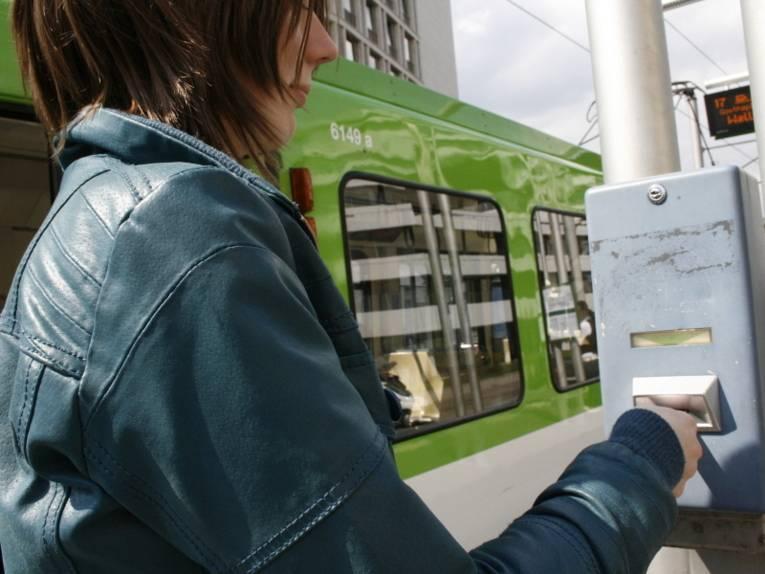 Frau entwertet Fahrkarte an blauem Stempelautomaten.