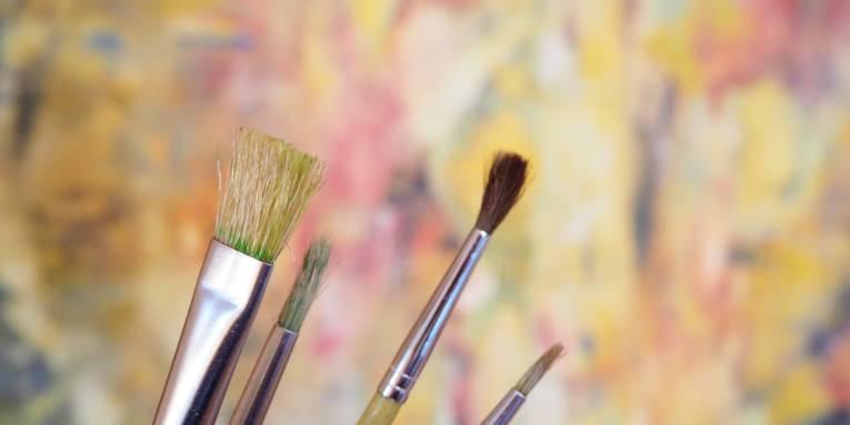 Verschiedene Pinsel vor einem farbigen Hintergrund.