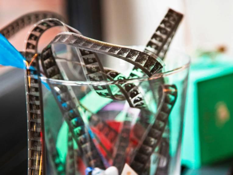 Ein Filmstreifen ist zur Dekoration in ein Glas gesteckt.