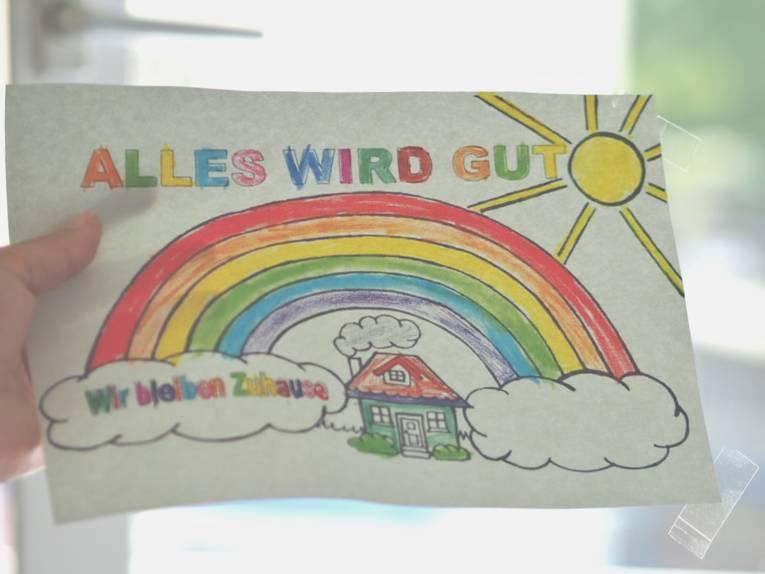 """Eine Hand klebt ein von Kinderhand ausgemaltes Bild in ein Fenster. Das Bild zeigt einen Regenbogen über einem Wohnhaus. Dazu der Text: """"Alles wird gut"""" und """"Wir bleiben zu Hause""""."""
