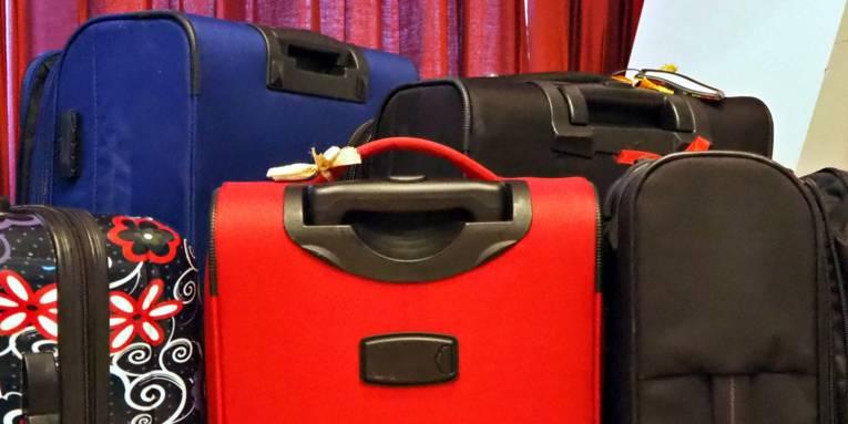 Um einen roten Koffer stehen weitere Koffer in verschiedenen Farben und einer mit einem floralen Muster.