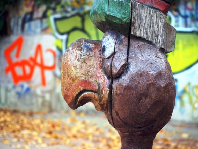Aus Holz geschnitzter Kopf eines Vogels auf einem Kinderspielplatz, im Hintergrund sind Graffitti.