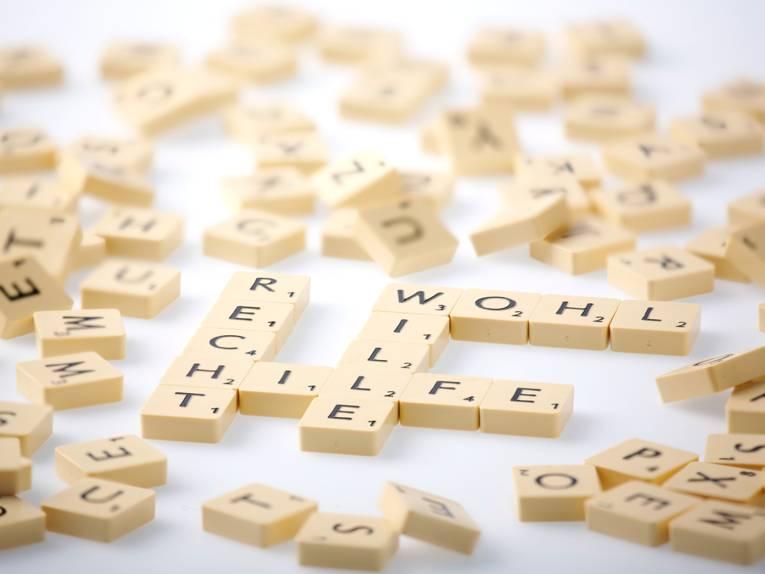 """Spielsteine sind auf einem Tisch zu den Worten """"Recht, """"Wohl"""", """"Wille"""" und """"Hilfe"""" gelegt. Drumherum liegen weitere Spielsteine durcheinander."""