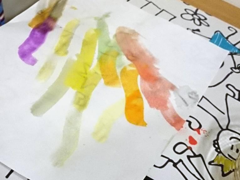Dicke Pinselstriche mit Wassermalfarben auf weißem Papier, darunter eine Malunterlage.