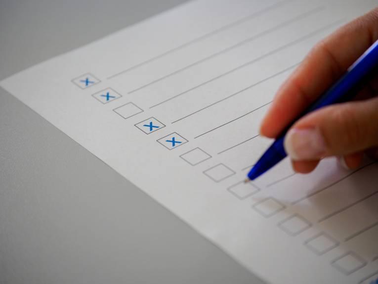 Ein Kugelschreiber in einer Hand über einem Papier mit leeren Zeilen zum Ausfüllen und mit Kästchen, in denen Häkchen gesetzt sind.
