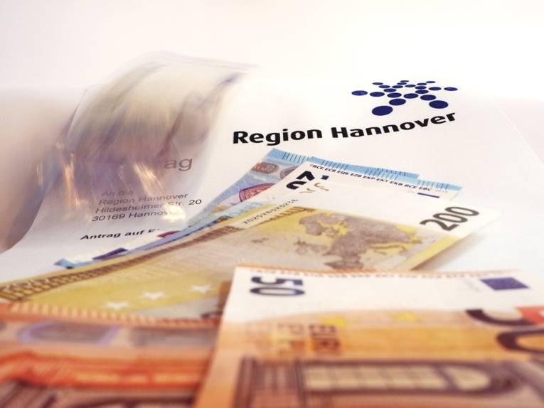 Geldscheine fallen auf ein Antragsformular der Region Hannover.