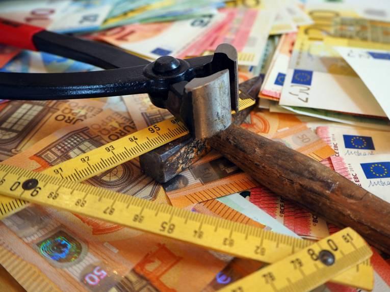 Eine Kneifzange, ein Hammer und ein Zollstock liegen auf ausgebreiteten Geldscheinen.
