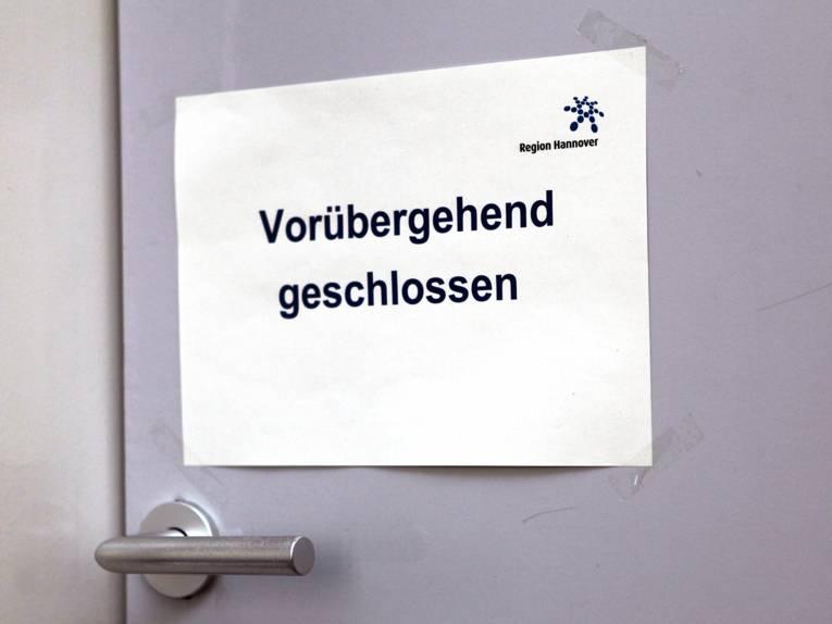 """Schild an einer Tür mit dem Text """"Vorübergehend geschlossen"""", das Regionslogo ist oben rechts."""
