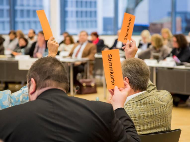 """Mitglieder der Regionsversammlung heben orangefarbene Pappkarten mit dem schwarzen Text """"Stimmkarte"""" in die Luft."""