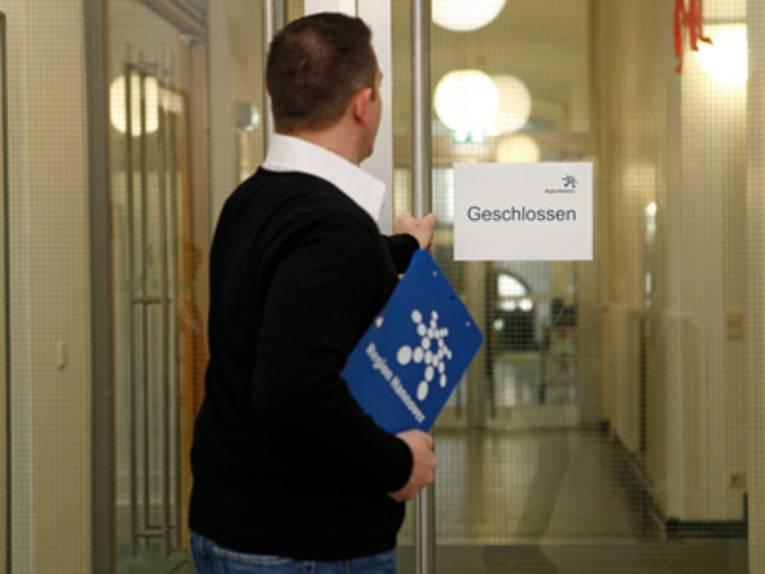 """Ein Mann vor einer Glastür mit der linken Hand am Türgriff. In der rechten Hand hält er ein Klemmbrett, welches mit dem Regionslogo versehen ist. An der Tür ist ein Zettel mit dem Hinweis """"geschlossen"""" befestigt."""