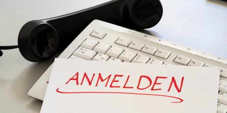 """Schriftzug """"Anmeldung"""" auf einer Tastatur, daneben liegt ein Telefonhörer."""
