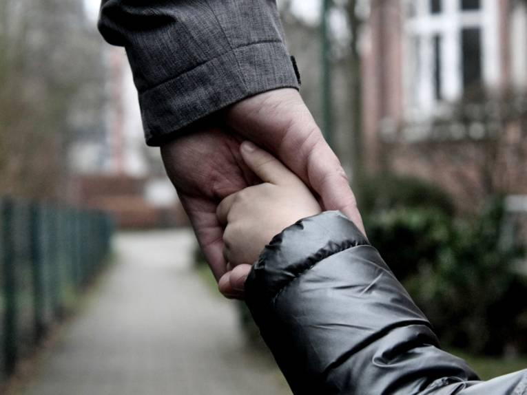 Die Hand eines Erwachsenen greift die Hand eines Kindes.
