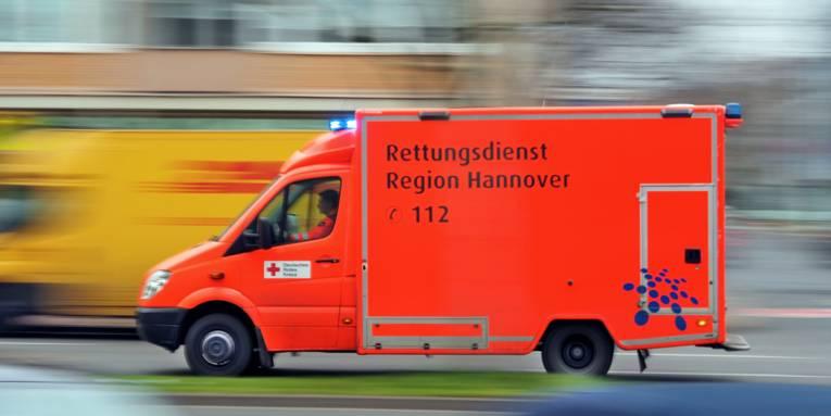 """Ein Rettungswagen fährt mit Blaulicht auf einer Straße und überholt andere Fahrzeuge. Auf der Fahrzeugseite steht """"Rettungsdienst Region Hannover. 112"""""""