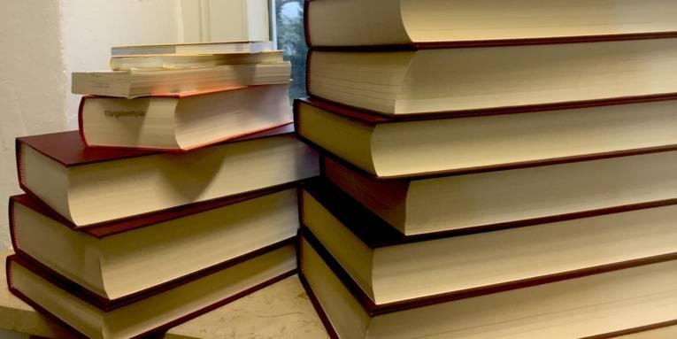 Zwei Bücherstapel in einer Fensterbank.
