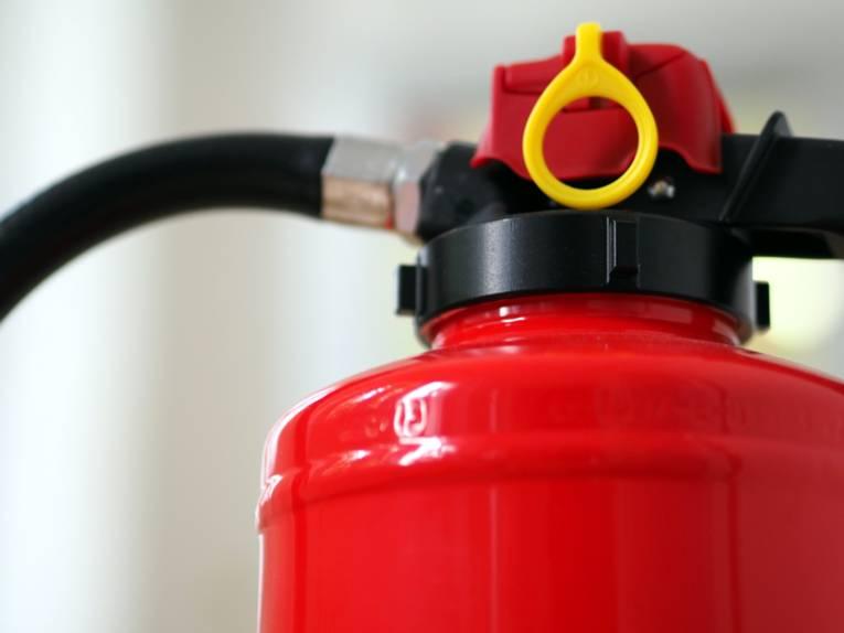 Oberer Bereich eines Feuerlöschers (Schaumlöscher, Brandklassen A und B) mit Schlauch und Sicherungseinrichtung.