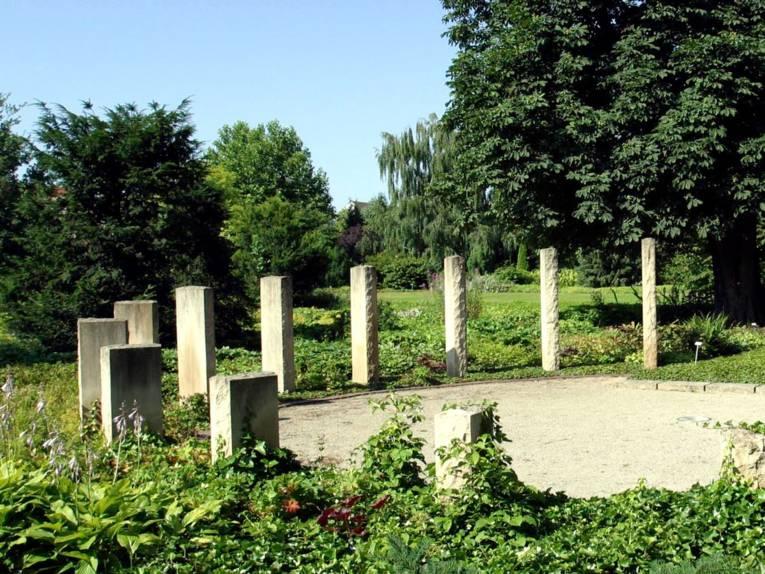 Grüne Wiese mit im halbkreis angeordneten, senkrecht stehenden, hellen Steinen.