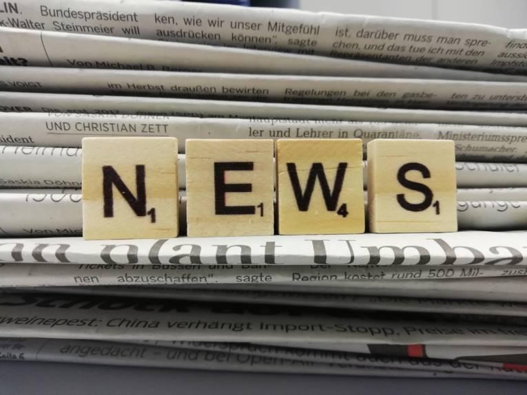 """Vier Holzwürfel mit Buchstaben drauf, die nebeneinander aufgestellt das Wort """"News"""" ergeben. Dahinter ist ein Stapel Zeitungen zu sehen."""