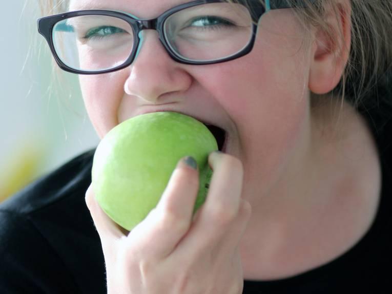 Eine Frau beißt in einen Apfel.