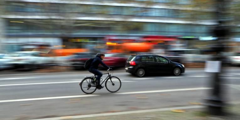 Ein Mann fährt auf einem Fahrrad durch den Stadtverkehr.