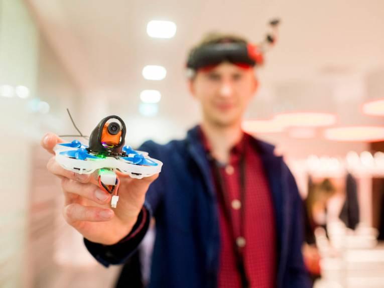 Mann hält Drohne in die Kamera