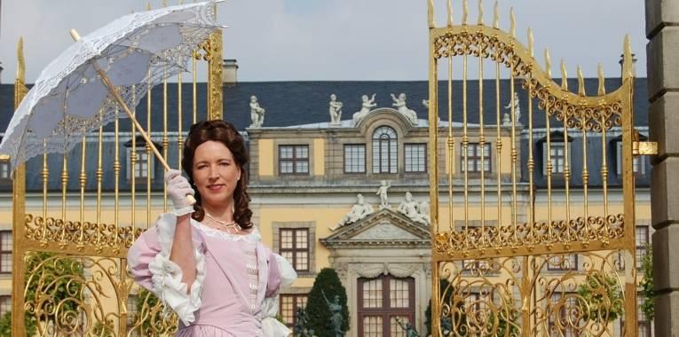 Eine Frau steht im Kostüm von Kurfürstin Sophie vor dem Goldenen Tor.