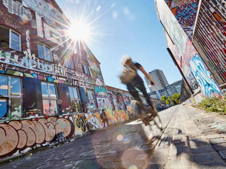 Fahrradfahrer vor einer Wand mit Graffiti.