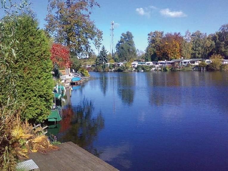 Ein See, gesäumt von herbstlich gefärbten Bäumen und einigen Wohnmobilen im Hintergrund.