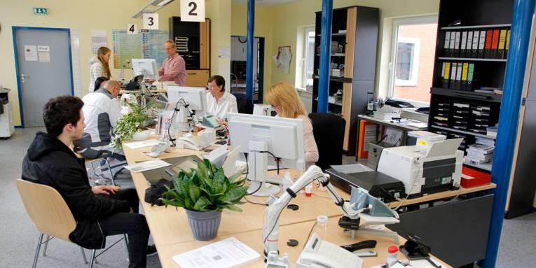 Im Bürgeramt Bemerode sitzen Einwohnerinnen und Einwohner an verschiedenen Servicestationen und werden dort von drei städtischen Beschäftigten bedient.