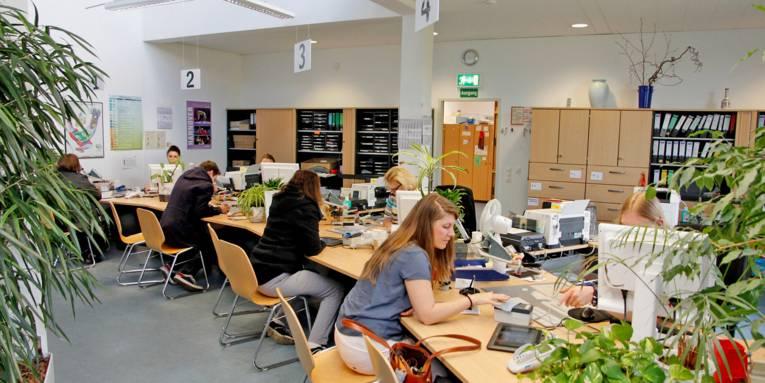 Kundinnen und Kunden sitzen gegenüber von Mitarbeiterinnen des Bürgeramtes