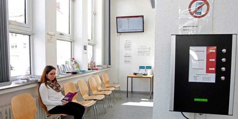 Im Wartebereich des Bürgeramtes Herrenhausen liest eine junge Frau in einer Broschüre, während die elektronische Anzeige Auskunft über die Bearbeitungsplätze gibt.