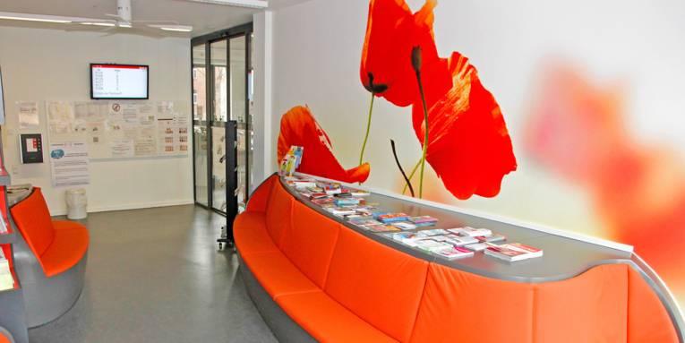 Ein großes geschwungenes Sofa und ein übergroßes Tulpenbild bestimmen den Wartebereich im Lindener Bürgeramt